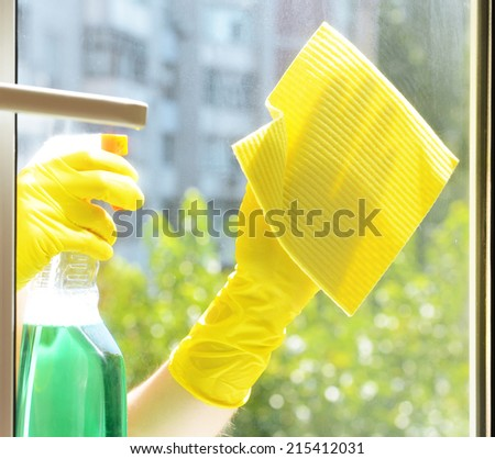 Cleaning windows with special rag and cleaner - stock photo