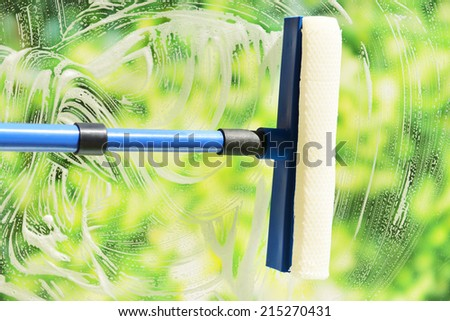 Cleaning windows with special squeegee - stock photo
