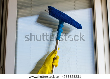 Cleaning windows with special squeegee in yellow gloves - stock photo