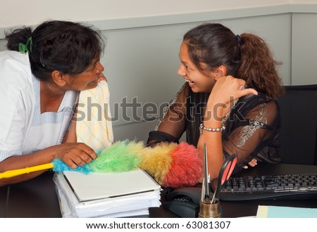 Cleaning woman and secretary talking gossip in the office - stock photo