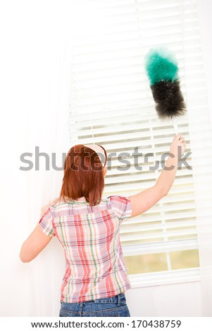 Cleaning: Woman Dusting Window Blinds.