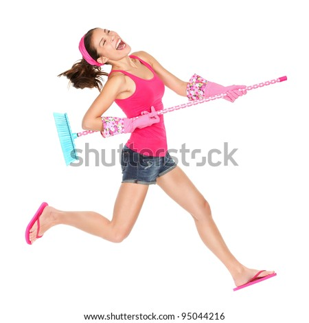 Cleaning woman jumping happy excited during spring cleaning fun. Funny energetic beautiful girl with cleaning broom playing air guitar isolated on white background. Multiracial Caucasian / Asian model