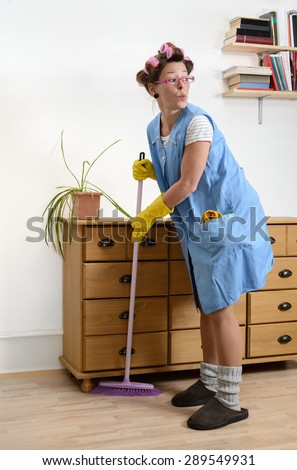Cleaning woman sweeping under the carpet - stock photo