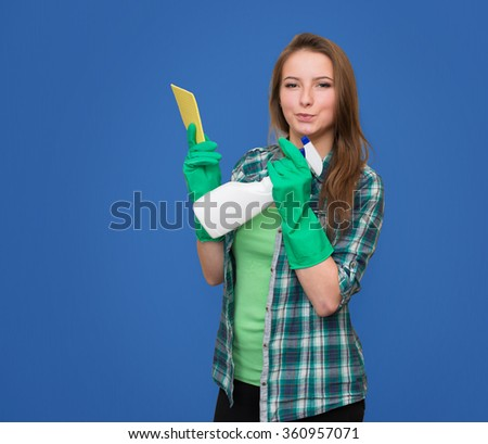 Cleaning woman with cleaning spray bottle happy and smiling. Beautiful cleaning girl isolated on blue background with copyspace. Mixed race woman. - stock photo