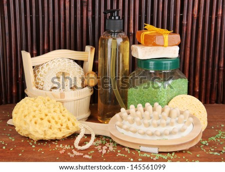 Cleanser, brush and cosmetics for shower on wooden table on bamboo background