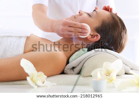 Cleansing facial skin, a woman in beauty salon.  Beautiful woman during treatments in the spa salon - stock photo