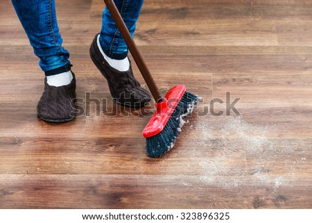 closeup broom and female foots cleaning woman sweeping wooden floor