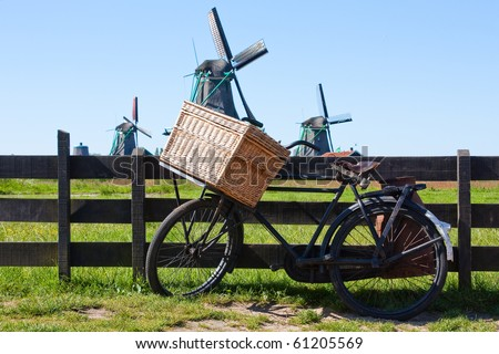 Clear and traditional landmark for Holland: bicycle and mills - stock photo