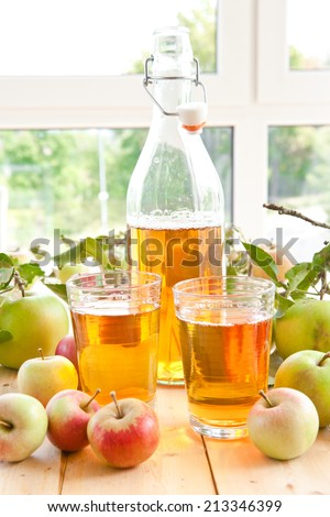Clear apple juice and a variety of fresh organic apples - stock photo