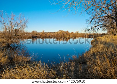 Clear blue lake with reflections in the Colorado prairie with tiny homes on the horizon - stock photo