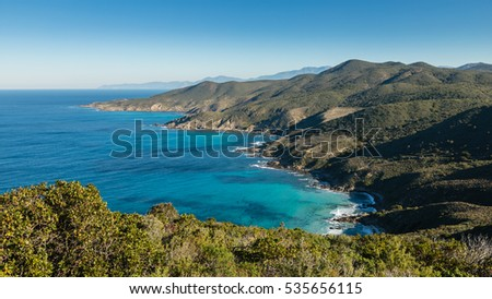 Clear blue sky above the turquoise Mediterranean sea on the coast of the Desert des Agriates in Corsica with maquis in the foreground and Cap Corse in the distance