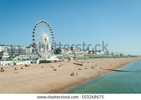 Clear blue sky over Brighton beach, UK and the tourist attractions of Madeira Drive - stock photo
