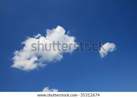 Clear blue sky with several clouds - stock photo