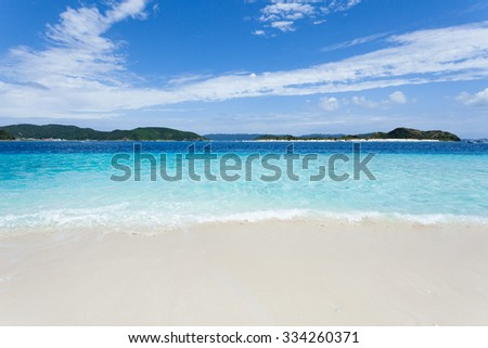 Clear blue tropical water wave lapping on white sand tropical beach, Zamami Island of the Kerama Islands National Park, Okinawa, Japan - stock photo