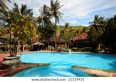 Clear blue water in round swimming pools with palms