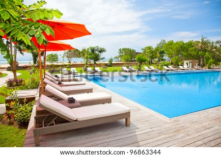 Clear blue water in swimming pool and tropical beach behind,  Indonesia - stock photo