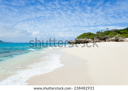 Clear blue water lapping on a deserted tropical island beach, Okinawa, Japan - stock photo