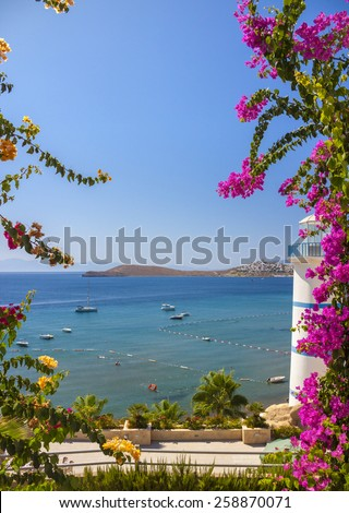 Clear blue waters and beautiful flowers can be seen past the Lighthouse at Ortakent in Turkey - stock photo