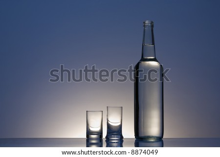 Clear bottle with two vodka glasses against blue gradient background. - stock photo