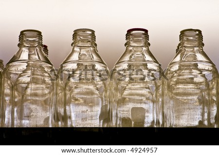 Clear bottles are lined up on a shelf. - stock photo
