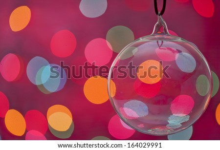 Clear Christmas Ornament lit with  bokah lighting. Copy space for holiday message or a card