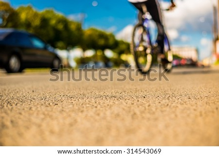 Clear day in the big city, a city street near the park, cyclist and a driver driving on the street. View from the level of asphalt - stock photo