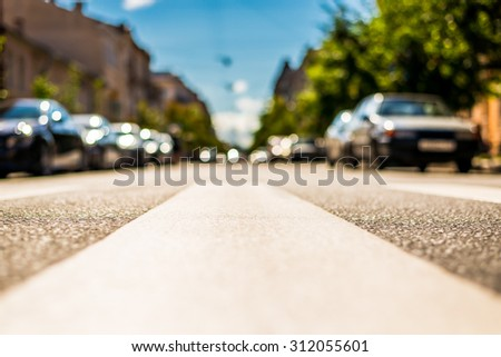 Clear day in the big city, city street with cars between old houses. View from the pedestrian crossing - stock photo