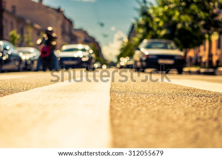 Clear day in the big city, the car and motorbike stopped in front of the pedestrian crossing. View from the pedestrian crossing, image in the yellow-blue toning - stock photo