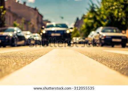 Clear day in the big city, the car stopped in front of the pedestrian crossing. View from the pedestrian crossing, image in the yellow-blue toning - stock photo