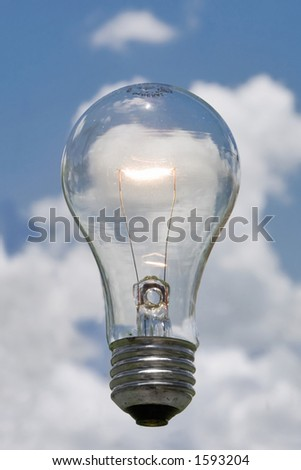 clear electric light bulb glowing against blue sky and puffy cloud background