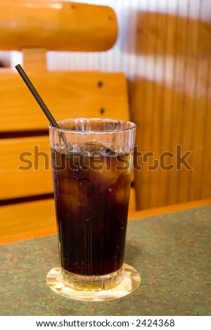 Clear glass with ice and cola-flavored drink sitting on coaster on table with black straw