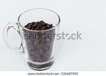 Clear glass with roasted coffee beans on the white background,select  focus. - stock photo