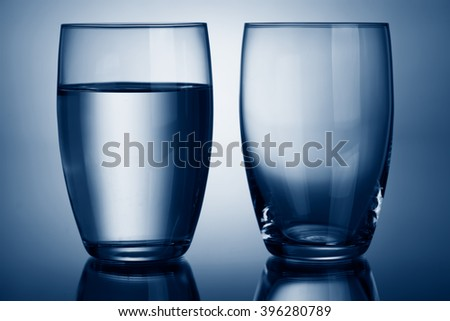 Clear glasses of water full and empty - stock photo