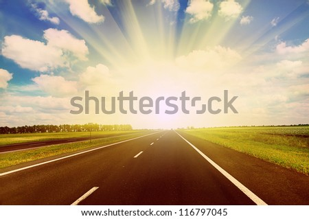 Clear highway under blue cloudy sky in sunset time - stock photo