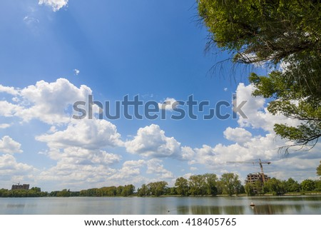 Clear lake reflecting blue sky with puffy white clouds in bright sunny day and constructions buildings with cranes far away - stock photo