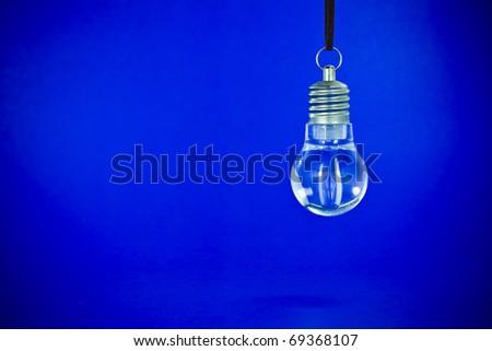Clear light bulb back lit by a blue light - stock photo