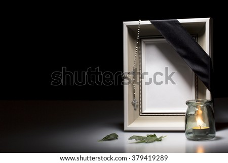 clear mourning frame with rosary, leaf and candle for sympathy card - stock photo