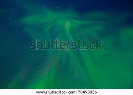 Clear night sky with lots of stars and dancing northern lights (Aurora borealis). - stock photo