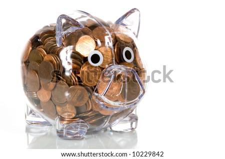 Clear plastic piggy bank stuffed full of pennies - stock photo