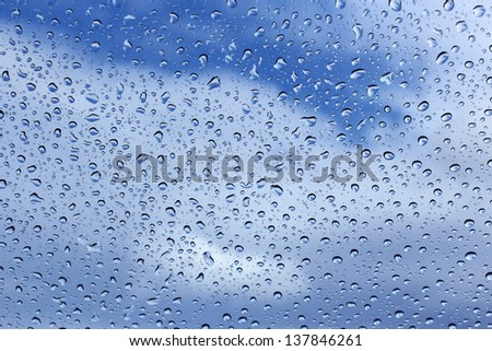 Clear raindrops on windscreen with blue cloudy sky background  ideal for  unique abstract wallpapers.