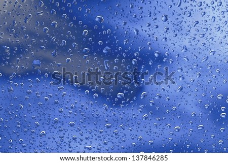 Clear raindrops on windscreen with blue cloudy sky background rendered in blue neon glow   ideal for  unique abstract wallpapers.
