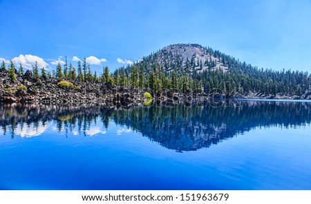Clear reflection of Wizard Island in the Sapphire Blue Waters of Crater Lake, Oregon - stock photo