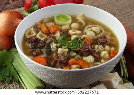 Clear soup with beef and noodles. Broth with carrots, onions various fresh vegetables in a pot