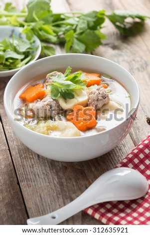 Clear Soup with Vegetables and Meatballs in white bowl. - stock photo