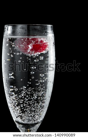 clear sparkling wine in a champagne flute with a red raspberry floating in it - stock photo