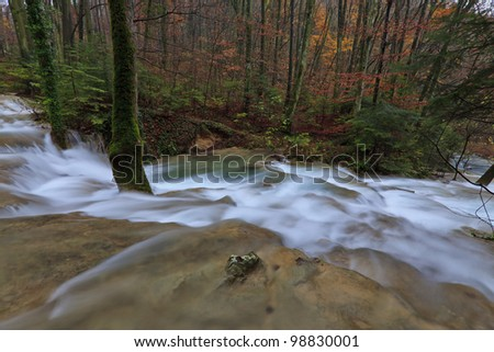 Clear stream and November foliage in remote mountain location - stock photo