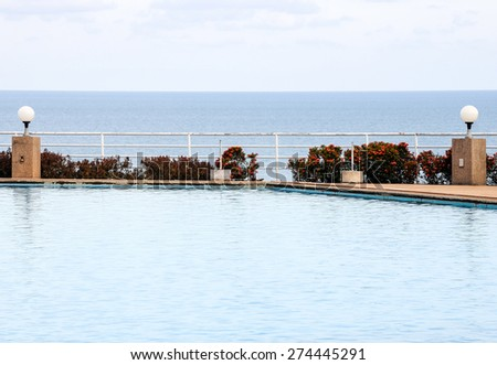 Clear swimming pool beside the tranquil sea. - stock photo