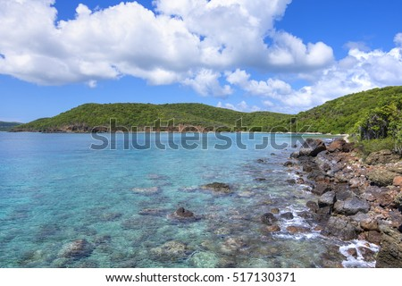 Clear turquoise blue water and rocky shoreline becoming sandy beach in the distance at Punta Soldado Beach on Puerto Rico island of Isla Culebra