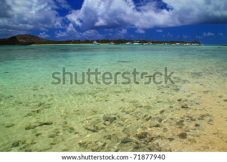 Clear turquoise water with blue sky and boats in the background - stock photo