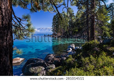 Clear, turquoise waters of Lake Tahoe with shoreline of pine forest and mountains  - stock photo